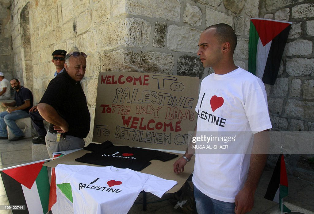 A Palestinian stands near a stall with T-shirts reading 'I love Palestine' that are offered to tourists as part of a campaign to raise awareness among foreign visitors about Palestinian indentity on May 24, 2013 in front of the Church of the Nativity in the West bank town of Bethlehem.