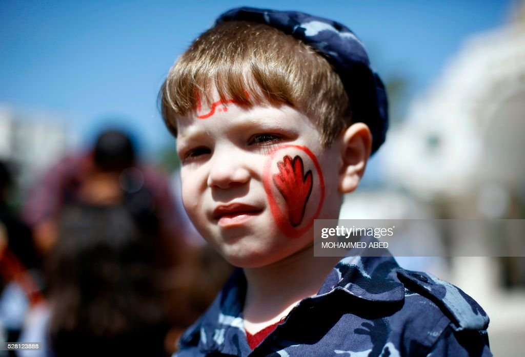 A Palestinian stands with a stop painted on his face during a day where the traffic police have increased presence in the streets to raise traffic awareness in Gaza City on May 4, 2016. / AFP / MOHAMMED