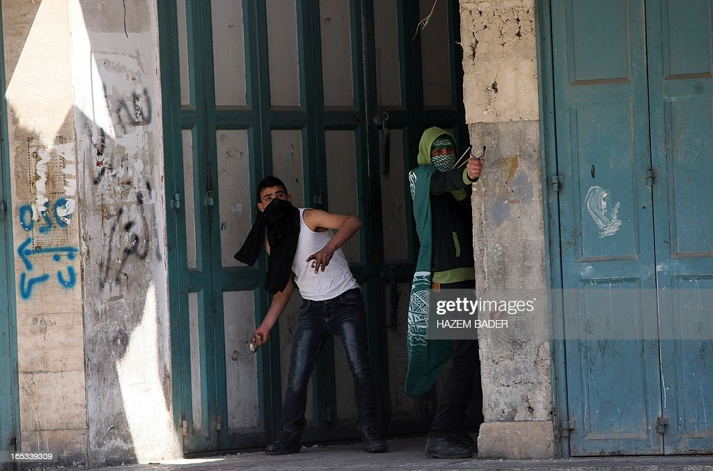 A Palestinian stone thrower bearing the Hamas flag (R) uses a sling shot to throw stones with his comrade towards Israeli security forces during clashes following a demonstration demanding the release of Palestinians detained in Israeli jails in the West Bank town of Hebron on April 3, 2013. Palestinians across the West Bank and Gaza were observing a general strike, with prisoners refusing food to mourn the death of a fellow inmate in an Israeli jail.