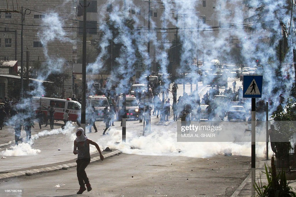 A Palestinian stone thrower runs from tear gas smoke fired by Israeli security forces (unseen) during clashes in the West Bank city of Bethlehem, on November 20, 2012. Palestinians clashed with Israeli security forces in the occupied West Bank as thousands marched demanding revenge for the killing of a protester the day before. AFP PHOTO/MUSA AL-SHAER