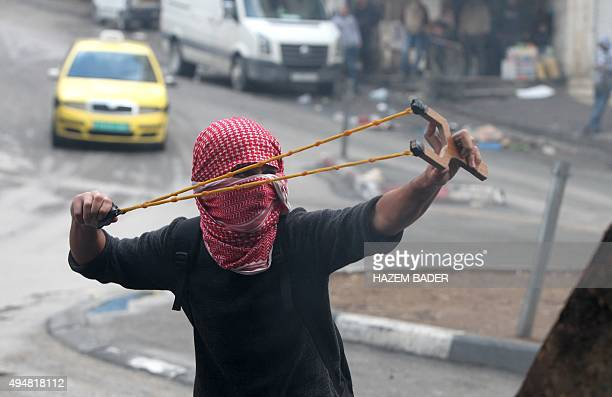 A Palestinian stone thrower uses a slingshot during clashes with Israeli security forces on October 29 2015 in the West Bank town of Hebron New knife...