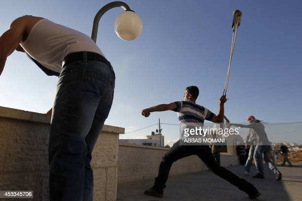 Palestinian stone throwers clash with Israeli security forces in the West Bank village of Silwad on August 8 2014 following a demonstration against...