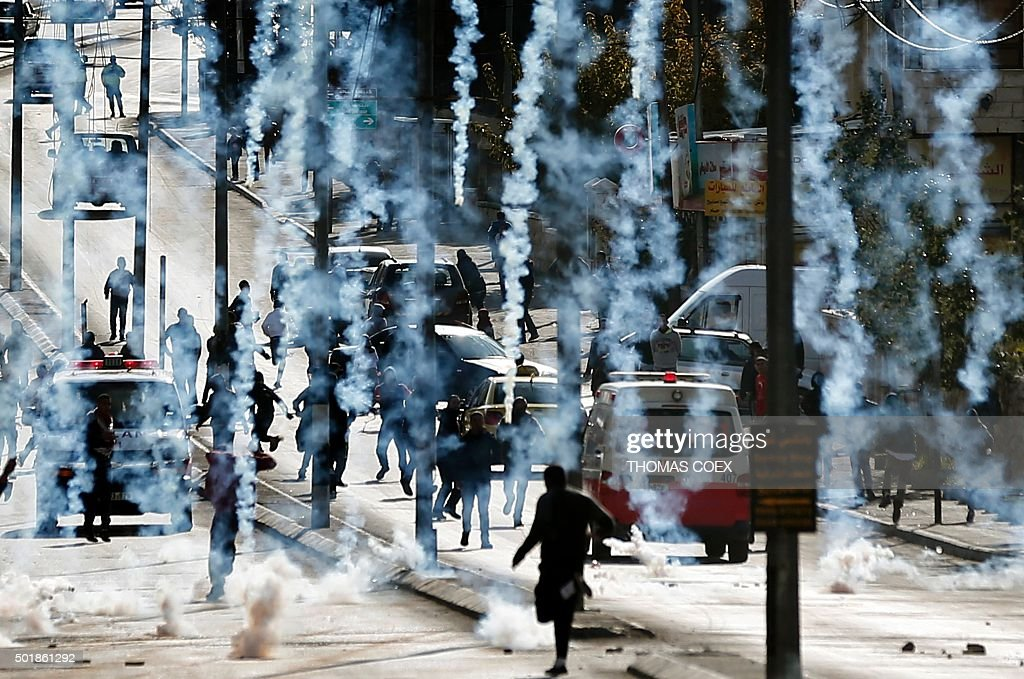 Palestinian stone throwers run to take cover after Israeli security forces fired tear gas canisters during clashes following a demonstration next to...