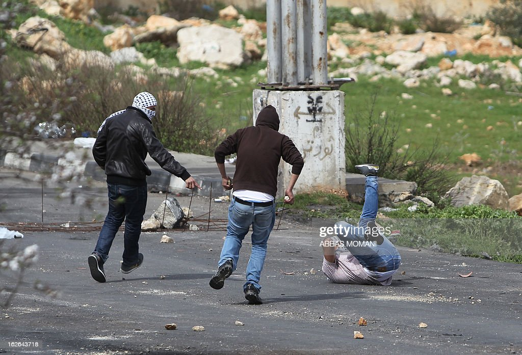 Palestinian stone throwers rush to help a wounded comrade during clashes with Israeli forces outside Israel's Ofer prison near Ramallah on February 25, 2013 after a protest in support of Palestinian prisoners on hunger strike in Israeli prisons. Palestinian president Mahmud Abbas said that Israel was deliberately seeking to stoke unrest in the occupied West Bank but that Palestinians would not be provoked.