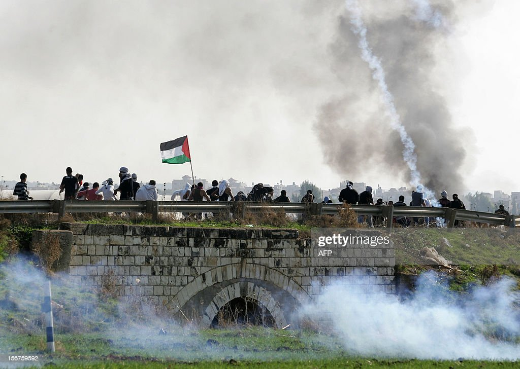 Palestinian stone throwers, waving their national flag, take cover from tear gas fired by Israeli security forces during clashes at the Jalama checkpoint near the West Bank city of Jenin, on November 20, 2012, following a demonstration against the ongoing Israeli military offensive on the Gaza Strip. Clashes erupted as thousands of demonstrators marched demanding revenge for the killing of a Palestinian protester the day before.