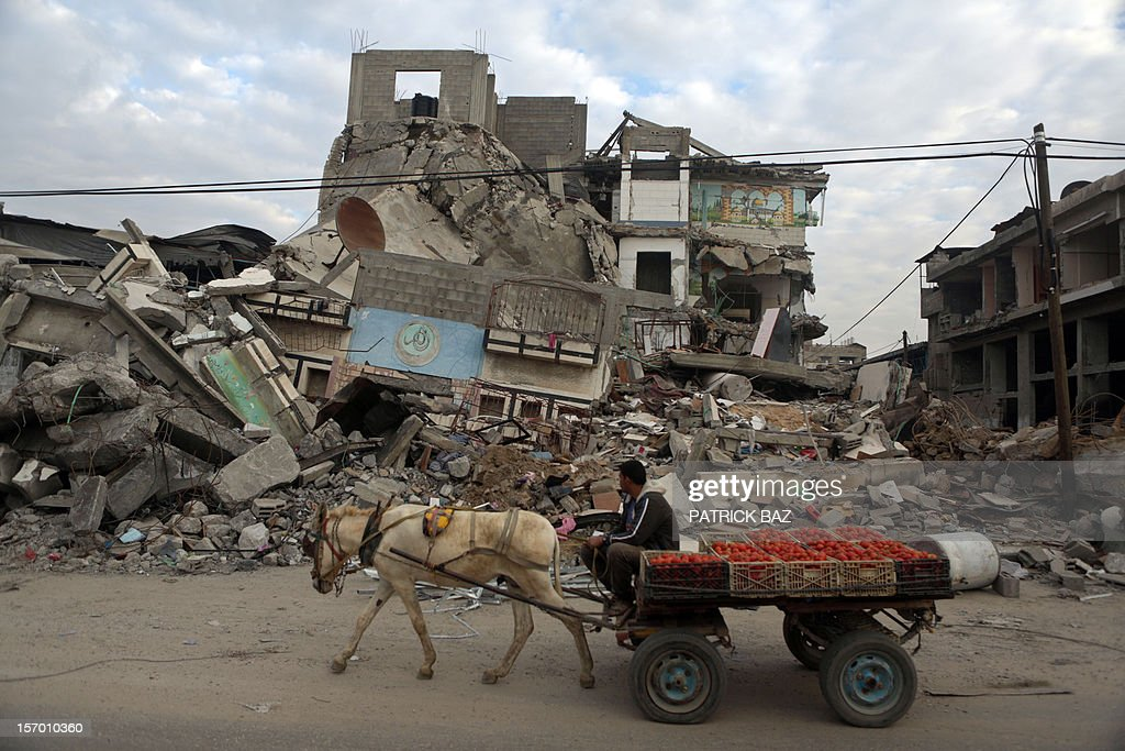 A Palestinian street vendor rides his donkey kart past a destroyed house in Gaza City on November 27, 2012.