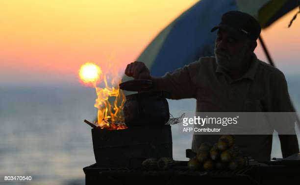Palestinian street vendor selling grilled corn boils a kettle of tea by the beach at sunset in Gaza City on June 29 2017 / AFP PHOTO / MOHAMMED ABED