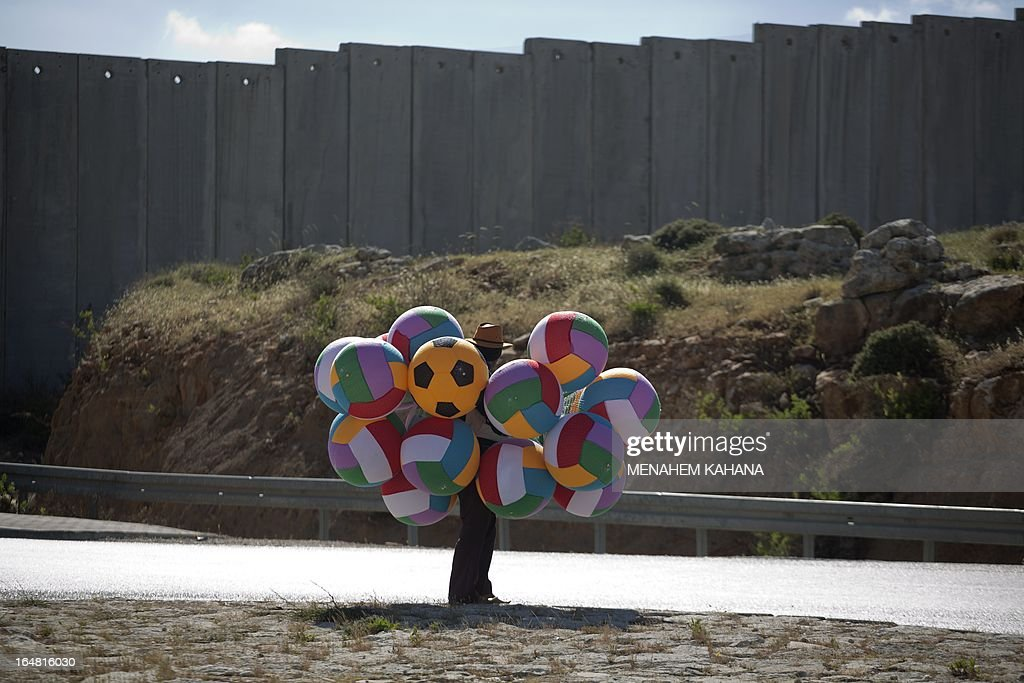 A Palestinian street vendor sells balloons next to the Israeli separation barrier in the West Bank village of Hizma, northeast of Jerusalem on March 28, 2013.