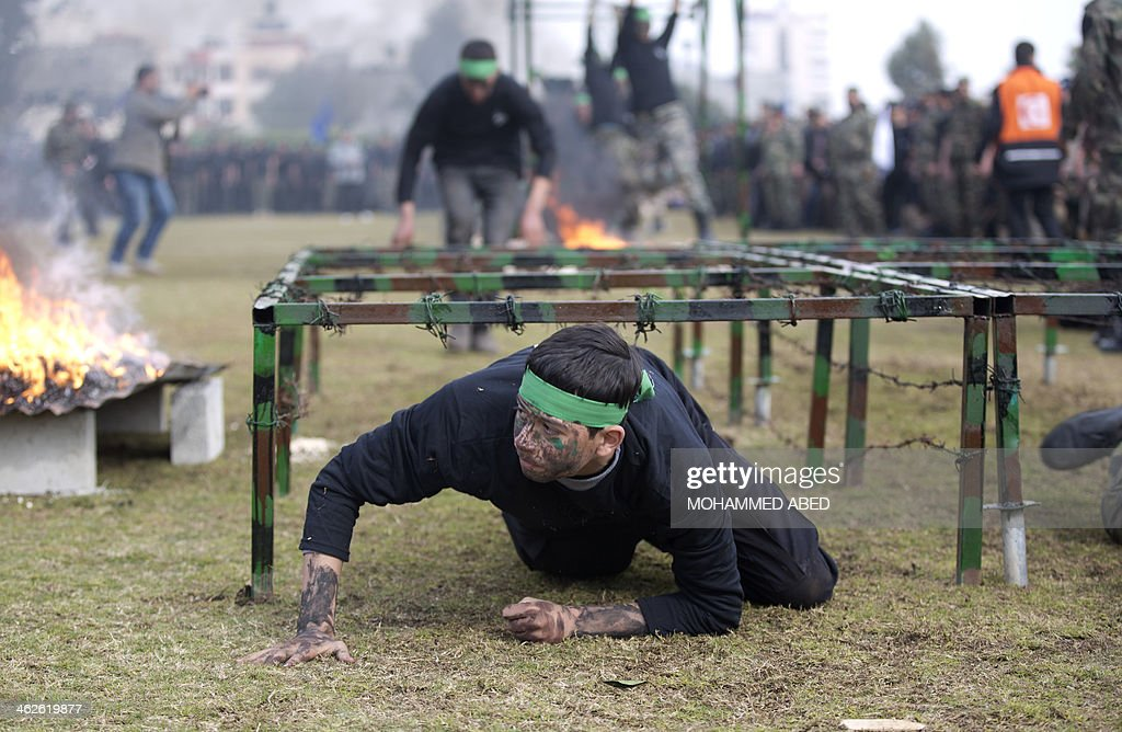 A Palestinian student crawls under a barbed wire obstacle during a graduation ceremony for a military-style training programme in Gaza City on January 14, 2014. Some 13,000 students joined the course, which is aimed at preparing them for 'liberating Palestine from Israel', Hamas officials said.