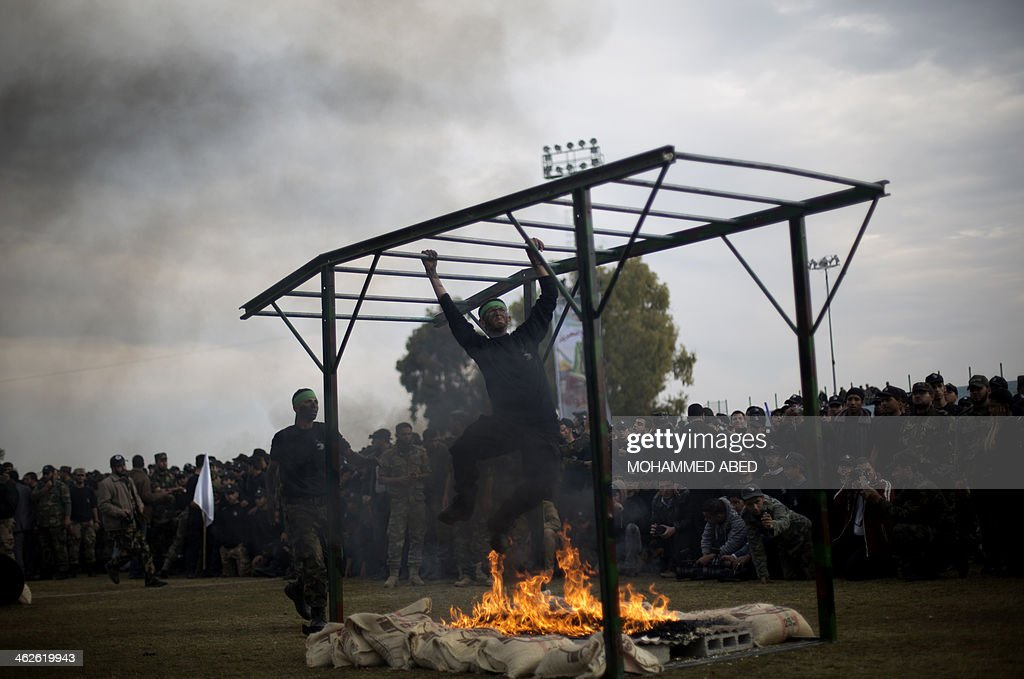 A Palestinian student crosses an obtsacle over a fire during a graduation ceremony for a military-style training programme in Gaza City on January 14, 2014. Some 13,000 students joined the course, which is aimed at preparing them for 'liberating Palestine from Israel', Hamas officials said.