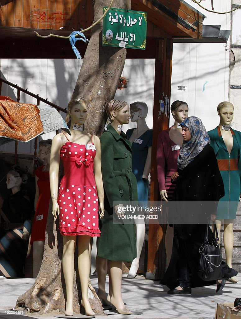 A Palestinian student from Al-Aqsa University walks past a dress shop next to the University campus in Gaza City on February 21, 2013. The university has denied reports that it has decided to impose a 'strict' Islamic dress code on female students.