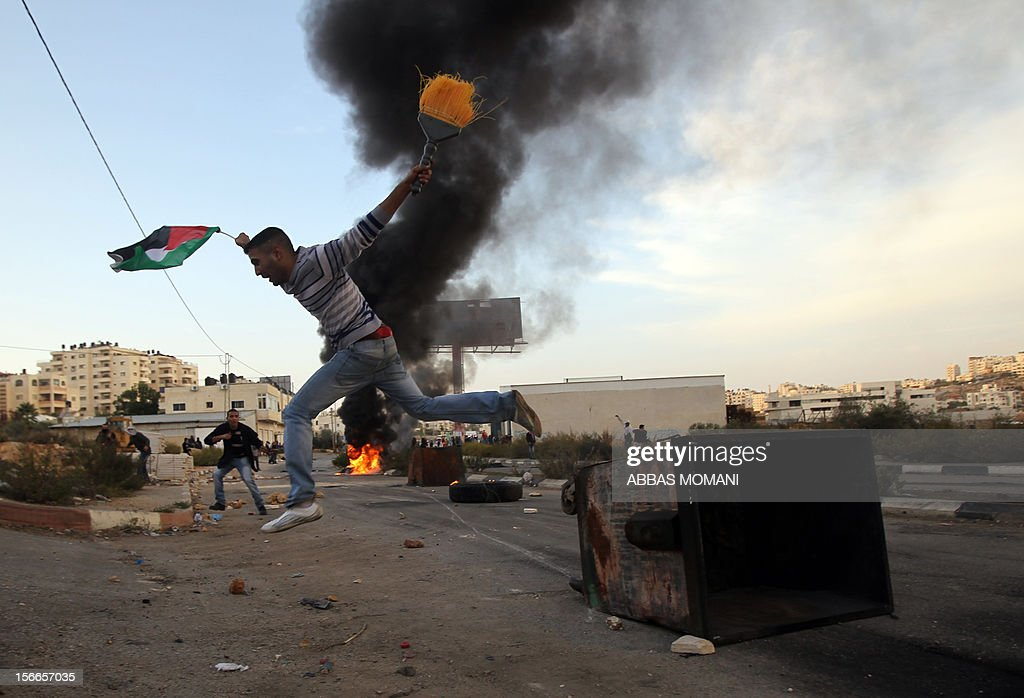 A Palestinian student from Birzeit University jumps over a dumpster during clashes with Israeli soldiers for the second consecutive day as they protest against the ongoing Israeli offensive on the Gaza Strip in the West Bank town of Betunia on November 18, 2012. Israel's Foreign Minister Avigdor Lieberman said that Israel would not negotiate a truce with Gaza Strip's Hamas rulers as long as rocket fire continues from the Palestinian enclave. AFP PHOTO/ABBAS MOMANI