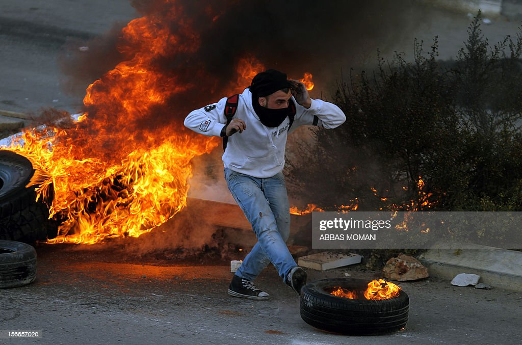 A Palestinian student from Birzeit University pushes a burning tire with his foot during clashes with Israeli soldiers for the second consecutive day as they protest against the ongoing Israeli offensive on the Gaza Strip in the West Bank town of Betunia on November 18, 2012. Israel's Foreign Minister Avigdor Lieberman said that Israel would not negotiate a truce with Gaza Strip's Hamas rulers as long as rocket fire continues from the Palestinian enclave. AFP PHOTO/ABBAS MOMANI