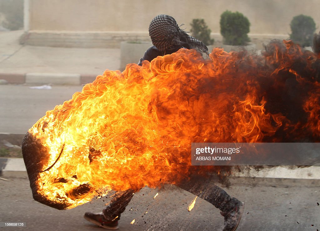 A Palestinian student from Birzeit University pushes a burning tire during clashes with Israeli soldiers for the second consecutive day as they protest against the ongoing Israeli offensive on the Gaza Strip in the West Bank town of Betunia on November 18, 2012. Israel's Foreign Minister Avigdor Lieberman said that Israel would not negotiate a truce with Gaza Strip's Hamas rulers as long as rocket fire continues from the Palestinian enclave. AFP PHOTO/ABBAS MOMANI