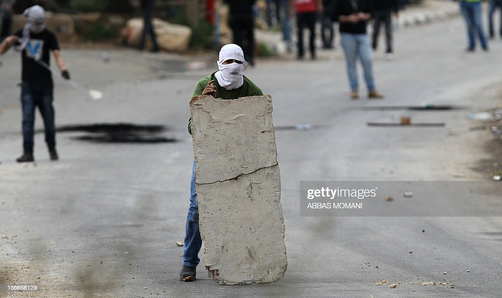 A Palestinian student from Birzeit University takes cover behind a behind a makeshift barrier during clashes with Israeli soldiers for the second consecutive day as they protest against the ongoing Israeli offensive on the Gaza Strip in the West Bank town of Betunia on November 18, 2012. Israel's Foreign Minister Avigdor Lieberman said that Israel would not negotiate a truce with Gaza Strip's Hamas rulers as long as rocket fire continues from the Palestinian enclave. AFP PHOTO/ABBAS MOMANI