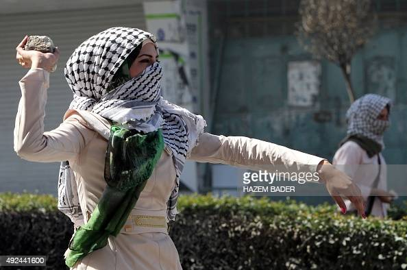 A Palestinian student from Hebron University throws a stone towards Israeli soldiers and border police during clashes after the Palestinian...