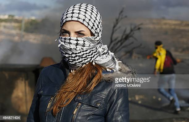 A Palestinian student from the Birzeit University her face covered with the traditional chequerred keffiyeh is pictured during clashes between...