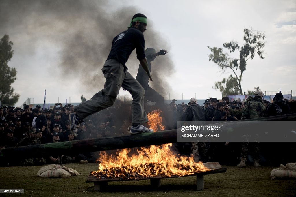 A Palestinian student jumps over an obtsacle next to a fire during a graduation ceremony for a military-style training programme in Gaza City on January 14, 2014. Some 13,000 students joined the course, which is aimed at preparing them for 'liberating Palestine from Israel', Hamas officials said.