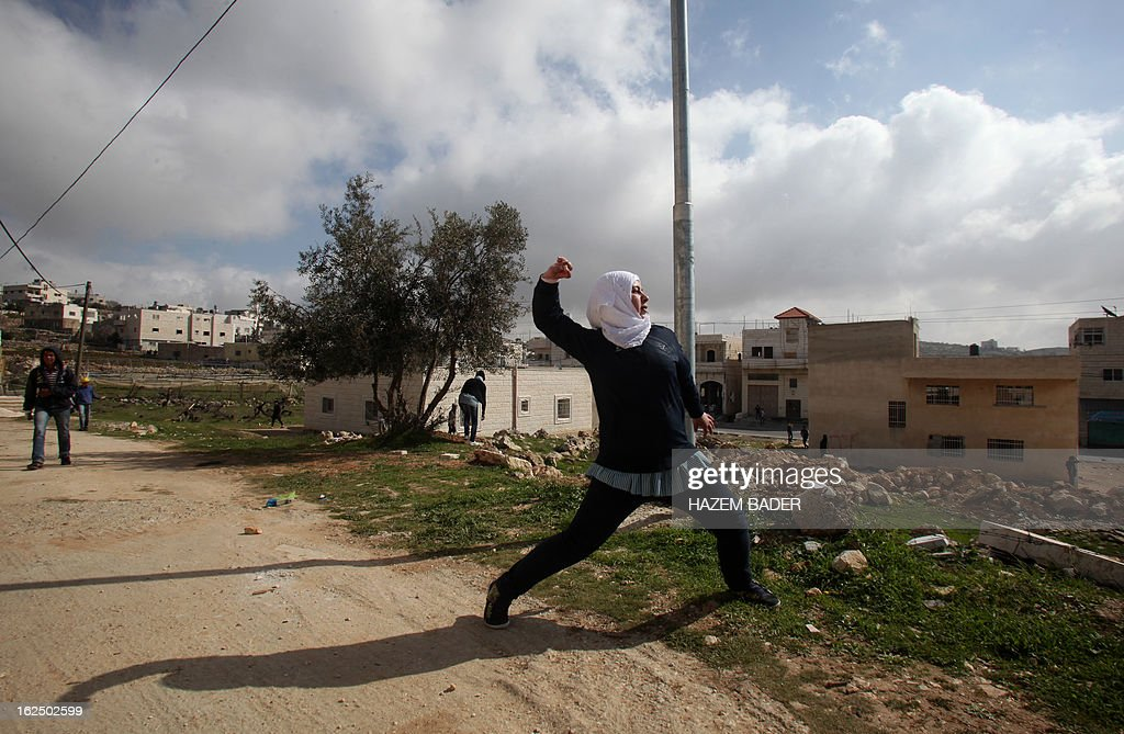 A Palestinian student throws stones towards Israeli security forces during clashes near the village of Saair, east the West Bank city of Hebron, on February 24, 2013 following the death of a Palestinian prisoner held in Israel. Some 3,000 Palestinians held in Israeli jails were staging a one-day hunger strike in protest at the death of the inmate Arafat Jaradat, an official said, as security forces clashed with demonstrators in the West Bank.