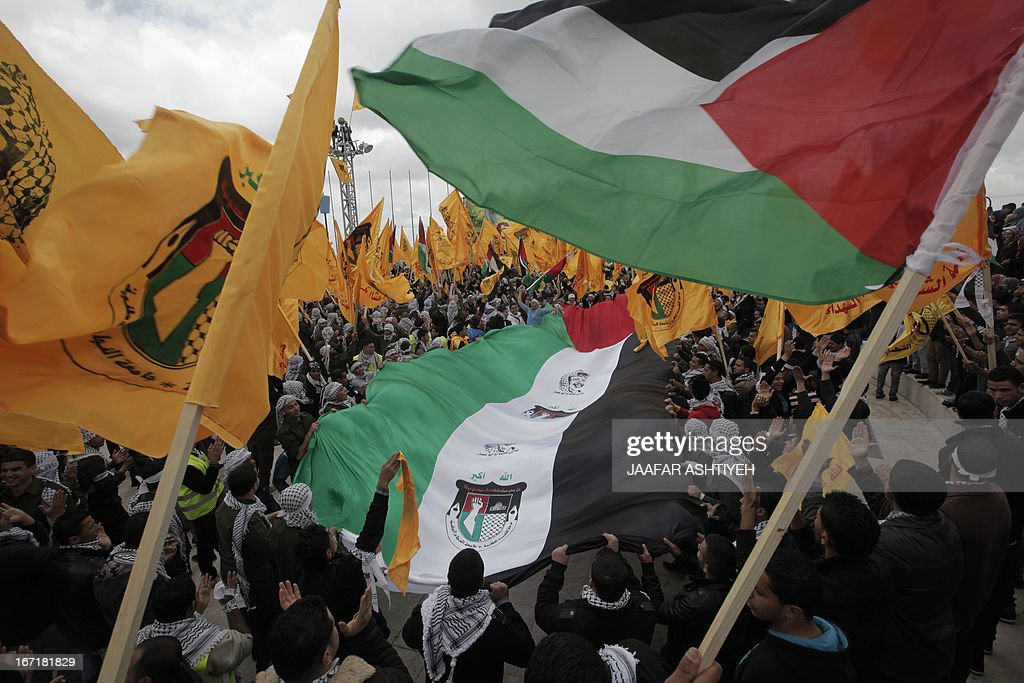 Palestinian students and supporters of Palestinian president Mahmud Abbas Fatah Movement, wave their national flag and the party's flag as they attend a pre-election rally for the student council at Al -Najah University, in the West Bank city of Nablus on April 22, 2013. The main competitors in the student elections represent opposing Palestinian political factions Hamas and Fatah.