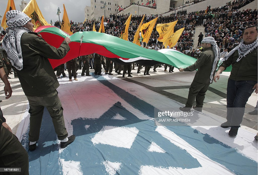 Palestinian students and supporters of Palestinian president Mahmud Abbas' Fatah Movement, stand on an Israeli flag as they wave both their national and the party's flag during a pre-election rally for the student council at Al -Najah University, in the West Bank city of Nablus on April 22, 2013. The main competitors in the student elections represent opposing Palestinian political factions Hamas and Fatah.
