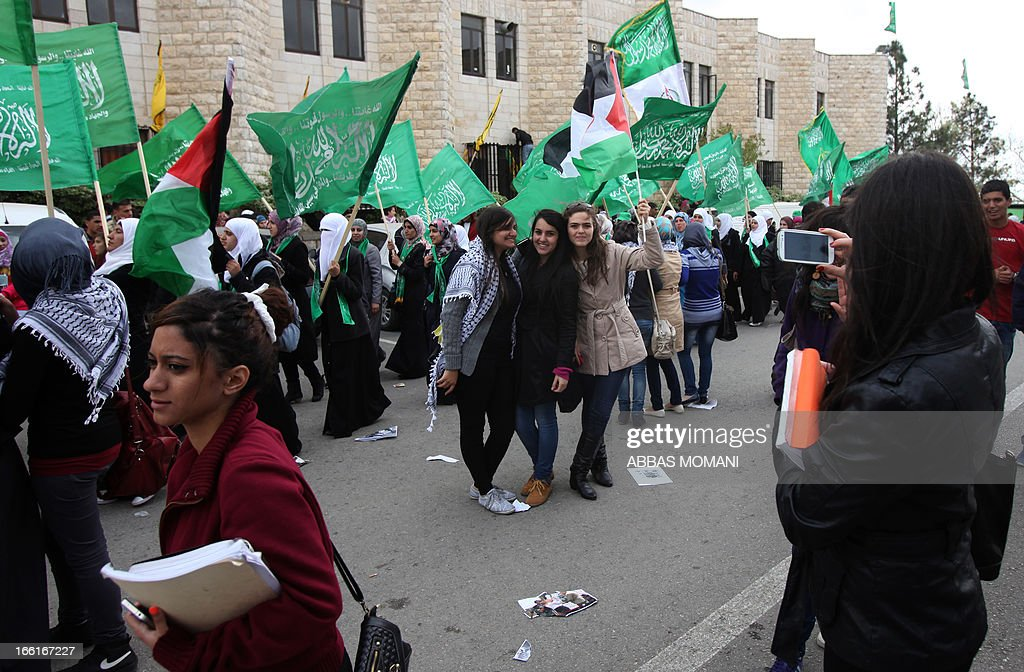 Palestinian students and supporters of the Hamas Islamist Movement, wave the party's flag as they attend a pre-election rally for the student council at Birzeit University, on the outskirts of the West Bank city of Ramallah on April 9, 2013. The main competitors in the student elections represent opposing Palestinian political factions Hamas and Fatah.