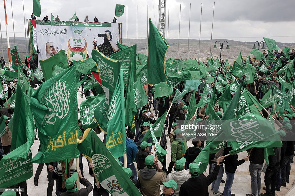 Palestinian students and supporters of the Hamas Movement, wave the party's flag as they attend a pre-election rally for the student council at Al -Najah University, in the West Bank city of Nablus on April 22, 2013. The main competitors in the student elections represent opposing Palestinian political factions Hamas and Fatah.