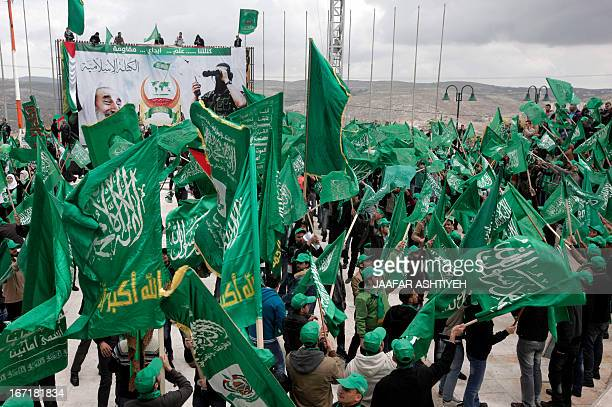 Palestinian students and supporters of the Hamas Movement wave the party's flag as they attend a preelection rally for the student council at Al...