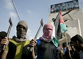 Palestinian students cover their faces with the trademark chequerred keffiyeh and hold up axes as a fellow protester waves a national flag during an...