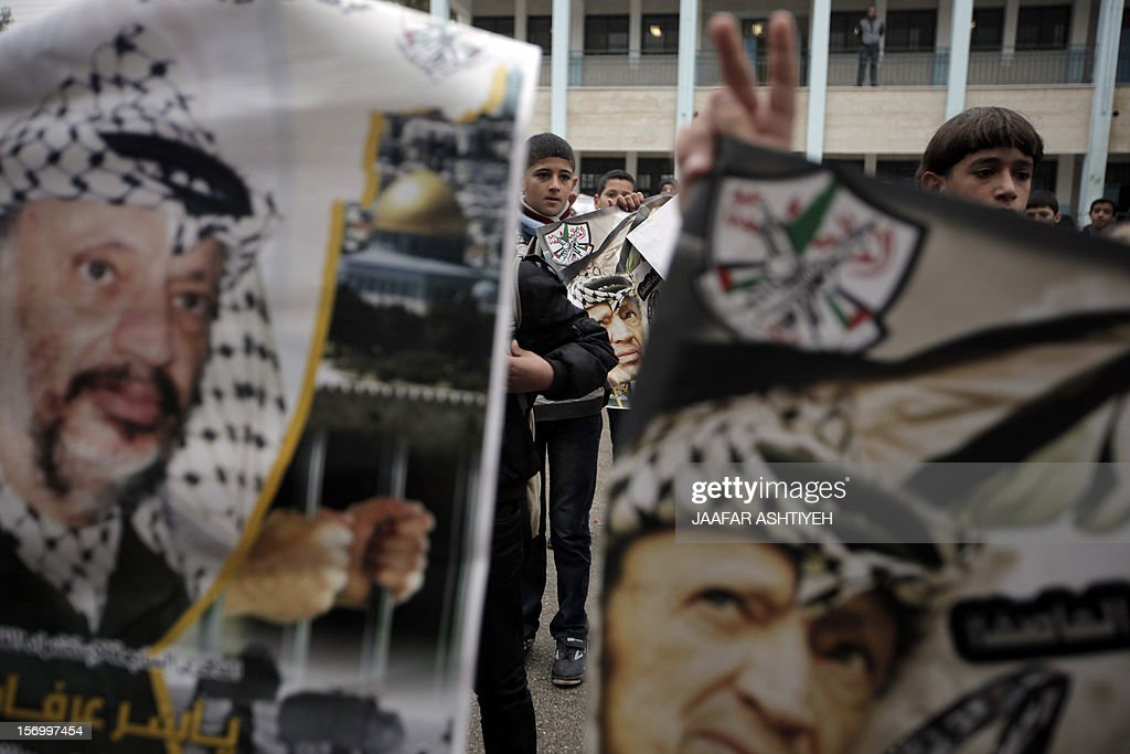Palestinian students flash the sign for victory and hold posters of late Palestinian leader Yasser Arafat during a memorial service for him at a school near the West Bank city of Nablus on November 27, 2012, as experts exhumed his remains to test for signs that he was poisoned. France opened a former murder inquiry into Arafat's death in late August at the request of his widow, Suha, and French judges in charge of the investigation arrived in Ramallah on November 25, to participate in the exhumation process. PHOTO