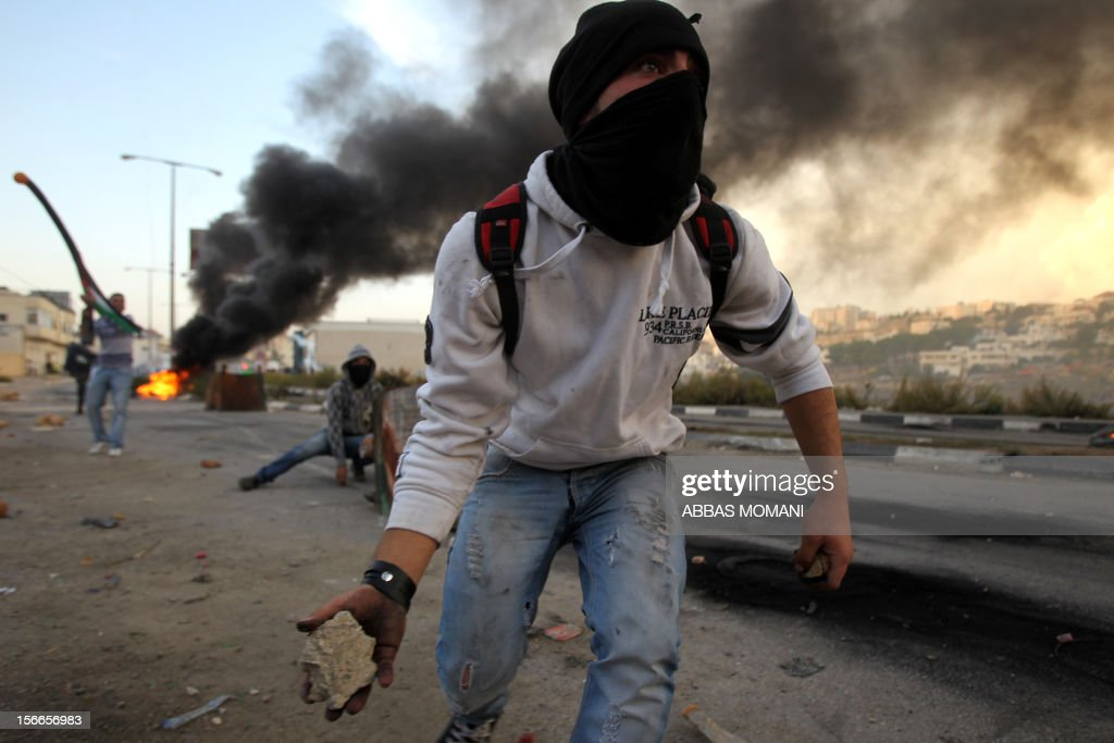 Palestinian students from Birzeit University clash with Israeli soldiers for the second consecutive day as they protest against the ongoing Israeli offensive on the Gaza Strip in the West Bank town of Betunia on November 18, 2012. Israel's Foreign Minister Avigdor Lieberman said that Israel would not negotiate a truce with Gaza Strip's Hamas rulers as long as rocket fire continues from the Palestinian enclave. AFP PHOTO/ABBAS MOMANI