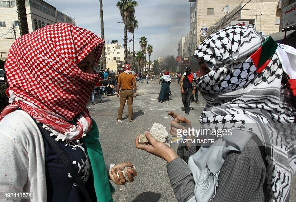 Palestinian students from Hebron University chat as they gather stones to throw towards Israeli soldiers and border police after the protesters...