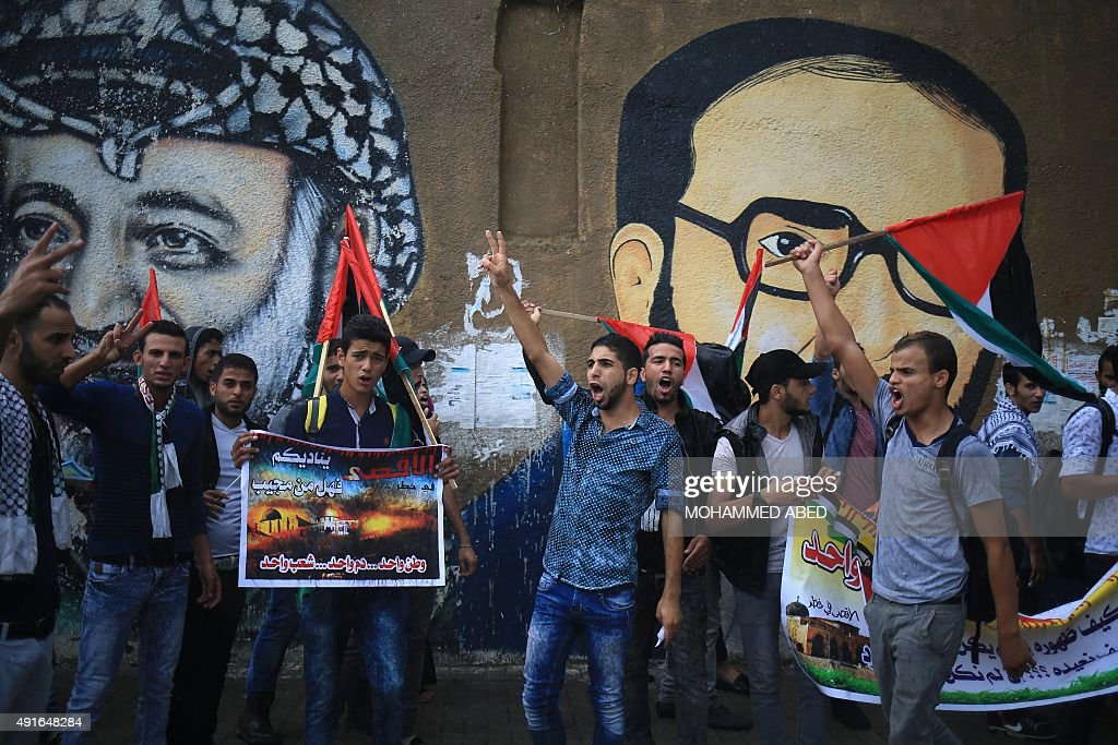Palestinian students hold national flags next to the murals of late Palestinian leader Yasser Arafat and late Islamic Jihad leader Fathi Shaqaqi...