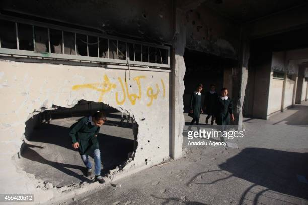 Palestinian students past through a damaged wall at Abu Kris primary school in Gaza City Gaza on September 14 2014 on the first day of the new school...
