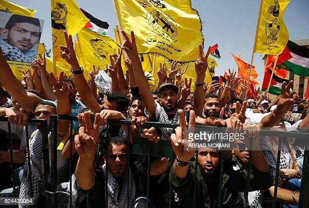 Palestinian students supporting the Fatah movement wave both their nationl and and a modified version of the movement's flag bearing a portrait of...