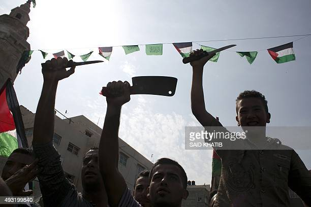 Palestinian students wave knives in the air during an antiIsrael protest in the city of Khan Yunis in the Southern Gaza Strip on October 18 2015...