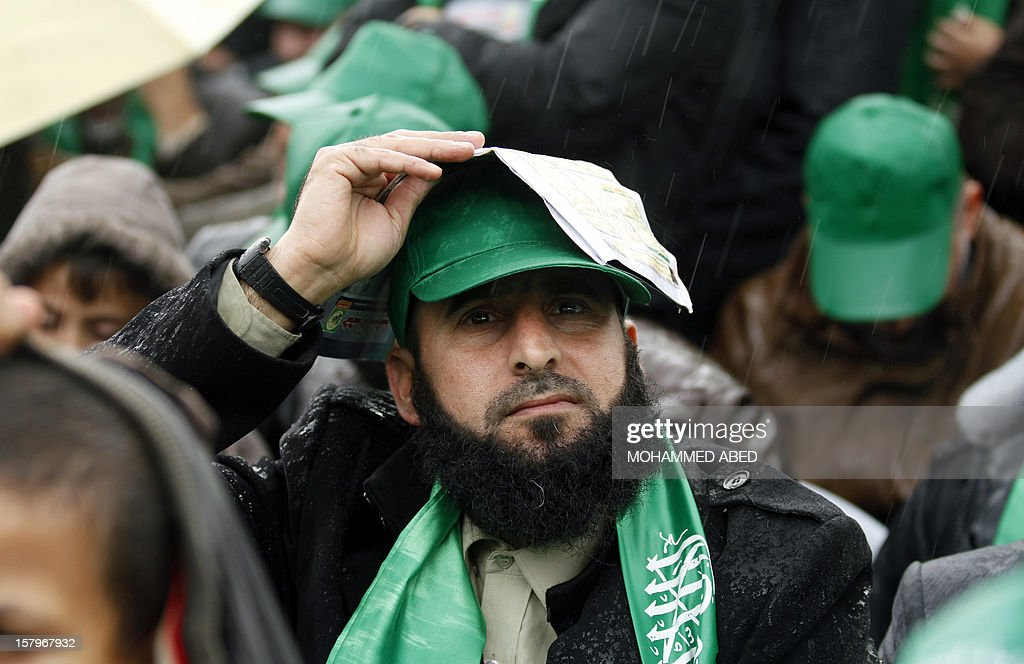 A Palestinian supporter of Hamas holds a piece of paper over his head to protect himself from the rain during a rally in Gaza City on December 8, 2012, to mark the 25th anniversary of the founding of the Islamist movement. More than 100,000 Palestinians gathered in Gaza for the rally to mark the occasion during which Hamas leader in exile Khaled Meshaal delivered a speech.