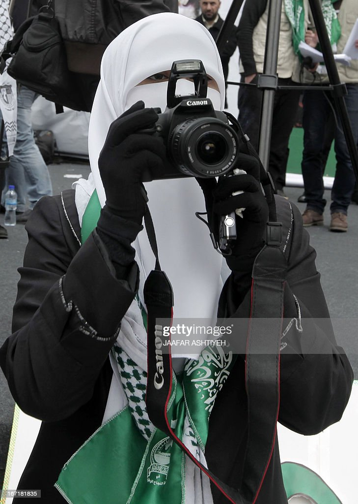 A Palestinian supporter of the Hamas Movement, takes photos as she attends a pre-election rally for the student council at Al -Najah University, in the West Bank city of Nablus on April 22, 2013. The main competitors in the student elections represent opposing Palestinian political factions Hamas and Fatah.