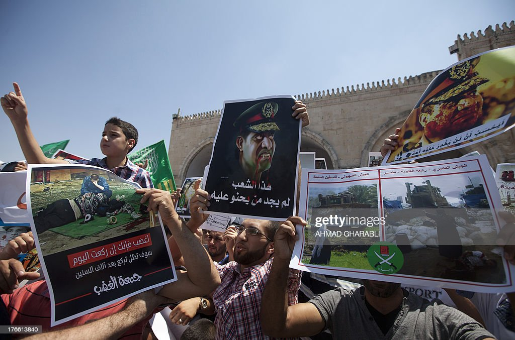 A Palestinian supporter of the radical Islamist movement Hamas holds a poster against Egypt's army chief Abdel Fattah al-Sisi (C) as he rallies alongside fellow demonstrators in support of Egypt's deposed president Mohamed Morsi and against the crackdown on on protest camps in Cairo, outside al-Aqsa mosque compound in Jerusalem on August 16, 2013. Egypt's Islamists called for a 'Friday of anger' after nearly 600 people were killed as security forces cleared their protest camps.