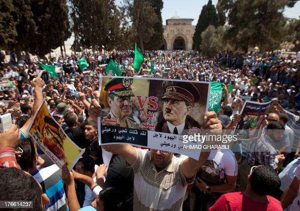 A Palestinian supporter of the radical Islamist movement Hamas holds a poster against Egypt's army chief Abdel Fattah alSisi which compares the...