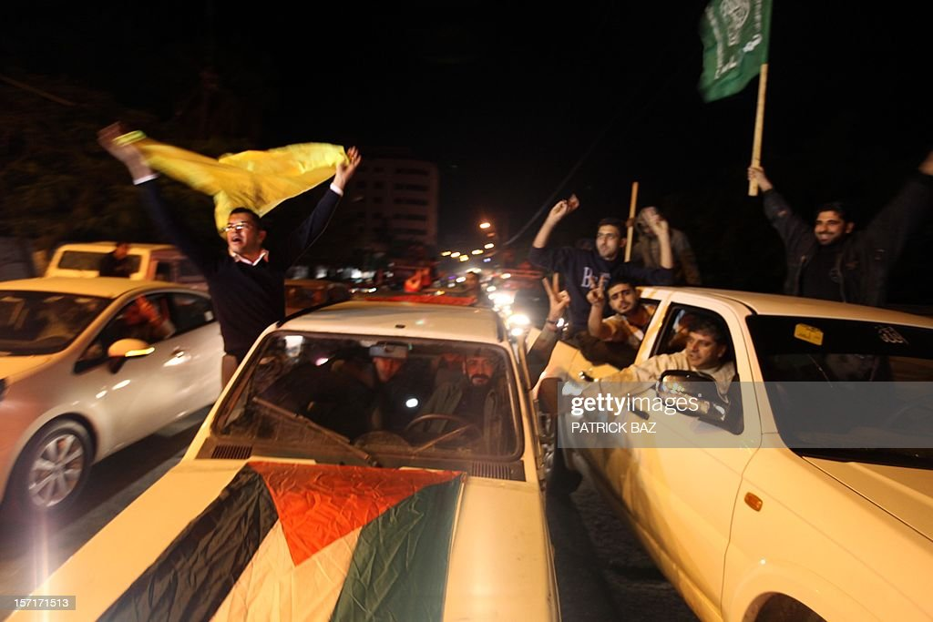 Palestinian supporters of Fatah (L) and Hamas (R) celebrate together in Gaza City early on November 30, 2012, after the UN General Assembly voted to upgrade them to a non-member state observer. The UN General Assembly on Thursday voted overwhelmingly to recognize Palestine as a non-member state, triggering scenes of joy on the streets of the Israeli-occupied West Bank. In a major defeat for the United States and Israel, Palestinian president Mahmud Abbas won what he called a 'birth certificate' for a Palestinian state, with the backing of 138 countries in the 193 member assembly.