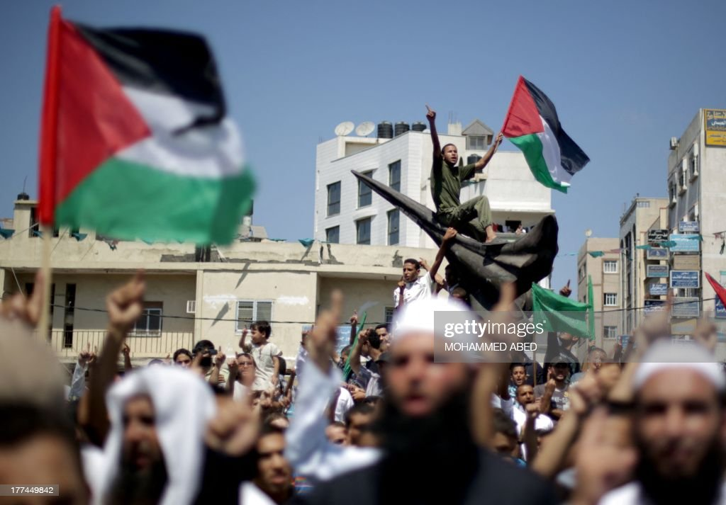 Palestinian supporters of Hamas and Islamic Jehad hold national flags shouting slogans during a protest against Palestinian-Israeli negotiations on August 23, 2013, in Gaza City. A senior Palestinian official accused on August 23 Israel of preventing the United States from taking part in peace talks, two days after a new round of meetings.