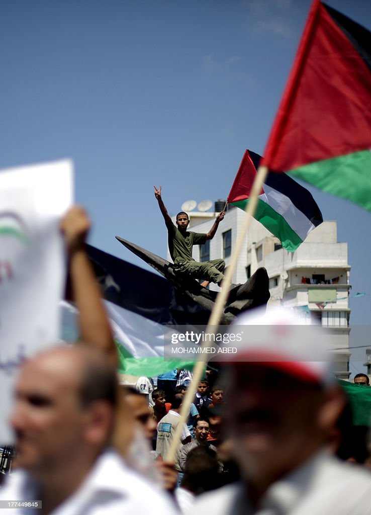 Palestinian supporters of Hamas and Islamic Jehad hold national flags during a protest against Palestinian-Israeli negotiations on August 23, 2013, in Gaza City. A senior Palestinian official accused on August 23 Israel of preventing the United States from taking part in peace talks, two days after a new round of meetings.