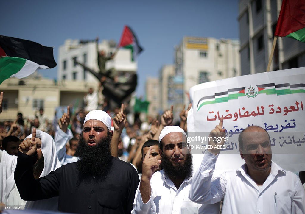 Palestinian supporters of Hamas and Islamic Jehad raise up their fingers shouting slogans during a protest against Palestinian-Israeli negotiations on August 23, 2013, in Gaza City. A senior Palestinian official accused on August 23 Israel of preventing the United States from taking part in peace talks, two days after a new round of meetings.