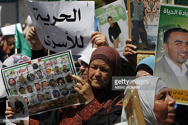Palestinian supporters of Hamas hold pictures of Palestinian prisoners on hunger strike in Israeli jails during a demonstration in their support in...