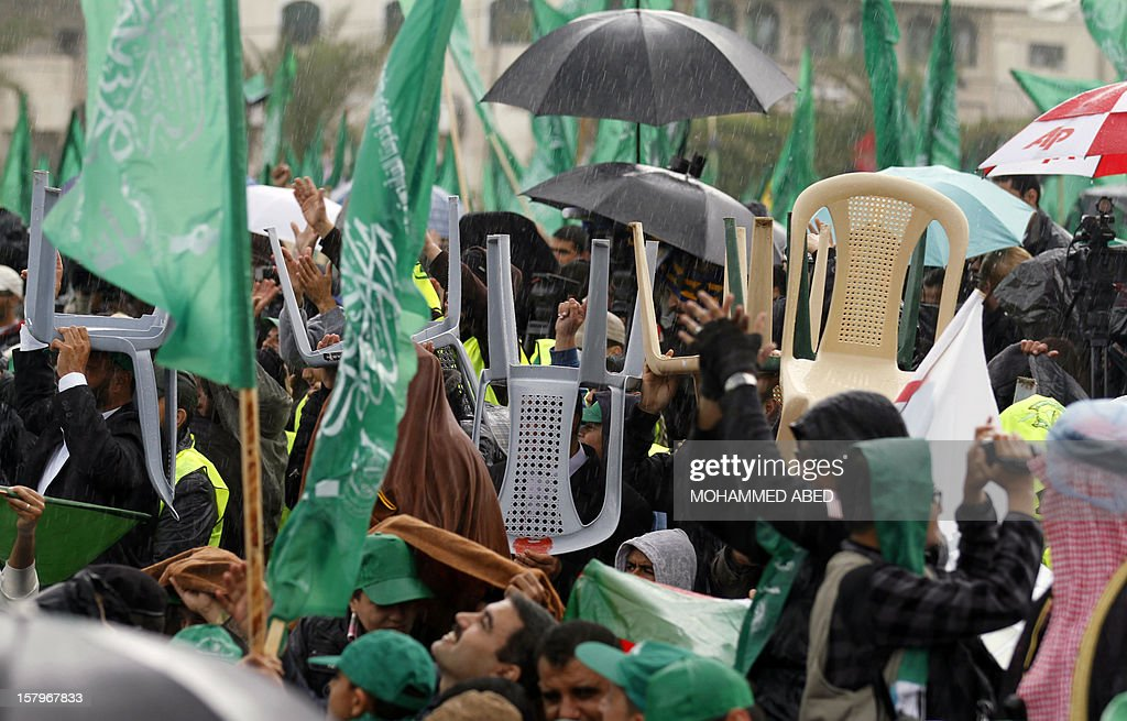 Palestinian supporters of Hamas hold up chairs and umbrellas to protect themselves from the rain during a rally in Gaza City on December 8, 2012, to mark the 25th anniversary of the founding of the Islamist movement. More than 100,000 Palestinians gathered in Gaza for the rally to mark the occasion during which Hamas leader in exile Khaled Meshaal delivered a speech.