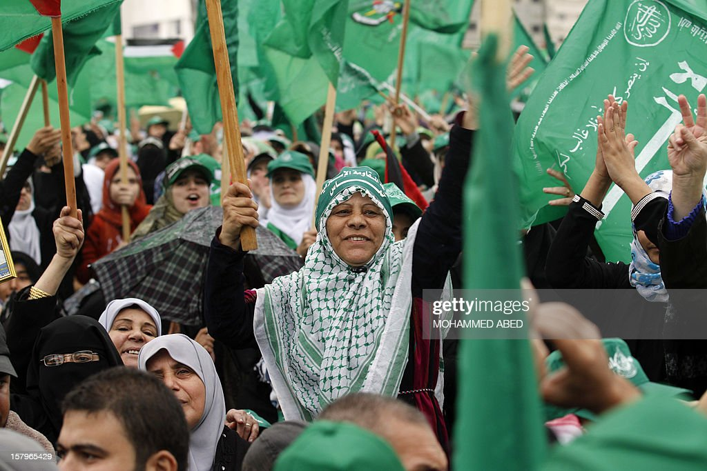 Palestinian supporters of Hamas wave green flags of the Islamist movement during a rally in Gaza City on December 8, 2012, to mark the 25th anniversary of the founding of Hamas. More than 100,000 Palestinians gathered in Gaza for the rally to mark the occasion during which Hamas leader in exile Khaled Meshaal delivered a speech.