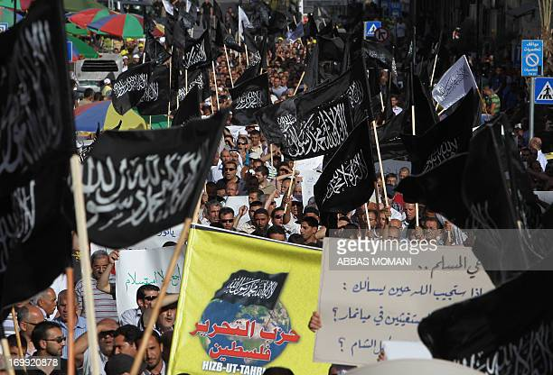 Palestinian supporters of Hizb utTahrir or the Islamic Liberation Party chant slogans and wave black and white flags with the religous writing 'There...