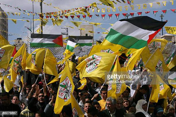 Palestinian supporters of president Mahmud Abbas and his ruling Fatah party wave the Palestinian and the Fatah flags during a rally in the West Bank...