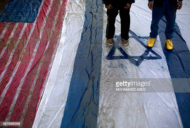 Palestinian supporters of the Islamic Jihad Movement walk on giant Israeli and US flags during a protest against resuming peace talks with Israel on...